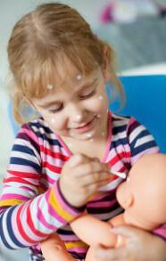 Маленькая девочка мажет куклу
