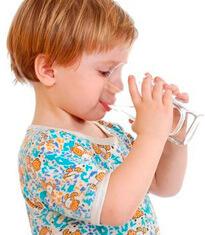 Мальчик пьет воду со стакана