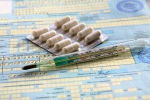 Таблетки и термометр лежат на бумаге
